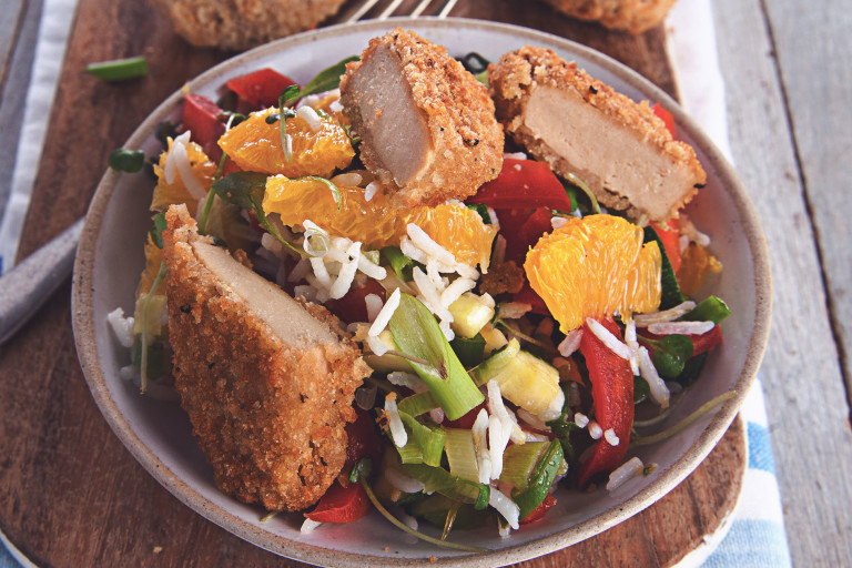 A salad made with lettuce, rice, orange segments, red pepper, cucumber and spring onions topped with Quorn Southern Fried Bites and herbs.