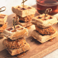 Five individual mini waffle sliders filled with Quorn Tex Mex Nuggets each with a bamboo toothpick through it arranged on a plank with syrup on the side.