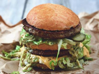 A double-decker burger with Quorn Meatless Gourmet Burgers, cheese, pickles, shredded lettuce, and plenty of sauce.