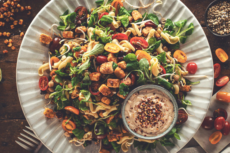 A picnic salad of pasta, black beans, chickpeas, sweetcorn, jalapeno, tomatoes, bean sprouts, and lettuce topped with marinated Quorn Pieces and sunflower seeds.