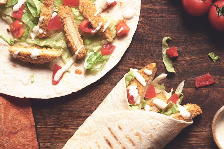 A table set with two Quorn Southern Fried Burger Wraps with a serving of creamy pepper sauce.