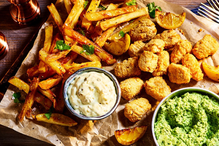 Quorn Vegan Fishless Scampi arranged on a board with chips, mushy peas, and tartare sauce on the side.