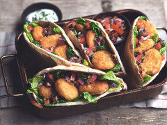 A tray of kebab style Quorn Meat Free Crispy Nuggets served in pitta bread with a yoghurt dip.