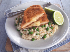 A Quorn Meatless Sharp Cheese Cutlet atop a bed of risotto with green peas, with a halved lime on the side.