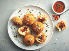 Five arancini on a white plate, two of white have been halved to show they're filled with Quorn Grounds, with a small bowl of tomato sauce on the side.