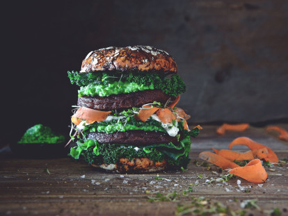 Veggie burger made with Quorn Ultimate Burgers layered with half a bun, pea hummus, kale, carrot strands and beansprouts