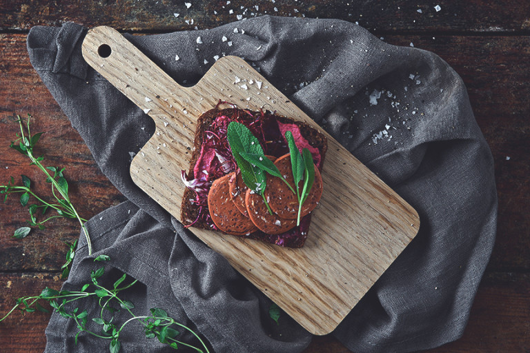 Vegan recipe made with a slice of rye bread topped with Quorn Vegan Pepperoni dressed with herbs served on a chopping board