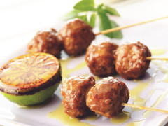 Three skewers with two meatballs each, drizzled with sauce with half of a charred lime on the side.