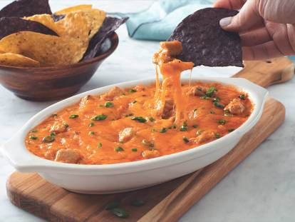 Vegetarian Quorn Buffalo Chicken Dip served in a dish with a nacho being dipped into the sauce