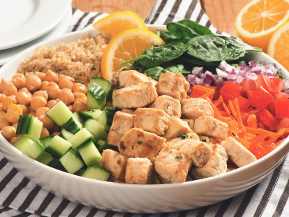 A white bowl with quinoa, spinach, diced red onion, shredded carrot, Quorn Pieces, diced cucumber, and chickpeas arranged in sections around the bowl and topped with two slices of lemon.