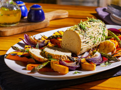 A summer vegetarian roast made with Quorn Meatless Roast topped with rosemary and lemon zest in the centre of a platter surrounded by roasted vegetables.