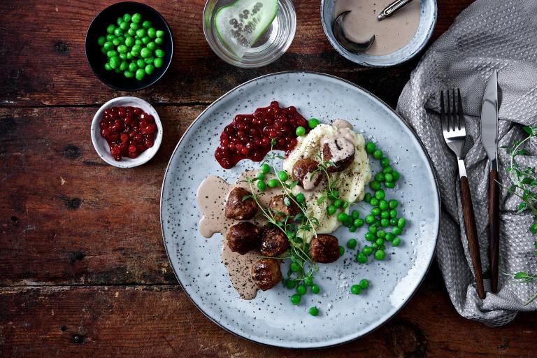 Veganska köttbullar med mos, gräddsås och rårörda lingon på tallrik.