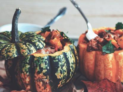 One green and one orange pumpkin, both topped and filled with vegetarian chili.