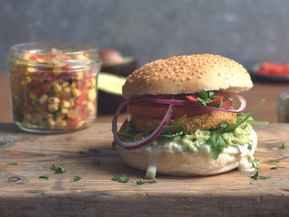 Vegan burger made with Quorn Vegan Hot and Spicy Burgers with salad, smashed avocado, tomato and onion in a bun