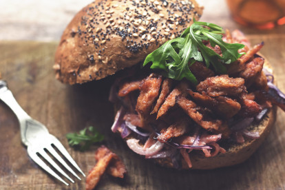 Meatless BBQ Pulled Quorn Fillets on top of a bed of salad in an open burger bun