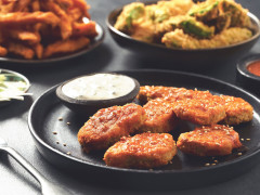 A plate of Quorn Vegan Buffalo Nuggets with Blue Cheese Sauce on a table containing homemade fries and crispy avocado wings.