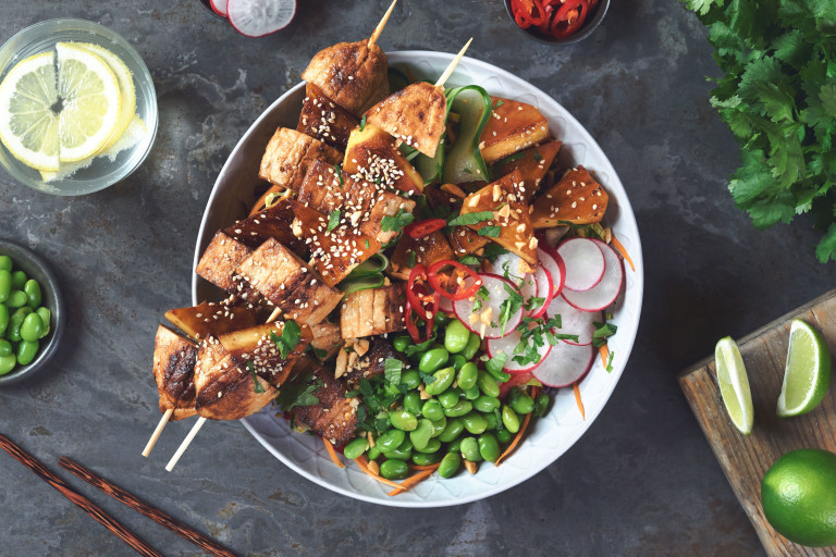 A bowl filled a salad of quinoa, lettuce, red cabbage, red pepper, carrot, spring onion, edamame, cucumber, and radish, topped with two skewers of grilled Quorn Fillet pieces and pineapple and coriander, chilli, sesame seeds, peanuts, and wedges of lime.