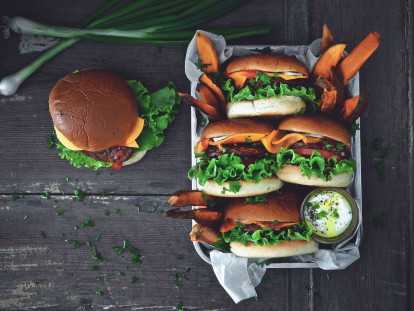 4 Quorn Classic Beef Style Burgers in buns served on a tray with sweet potato fries and a pot of mayonnaise with one burger on the table