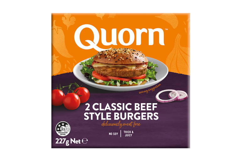 A box of Quorn Quarter Pounders showing a prepared and plated burger and product information on an orange and purple background.
