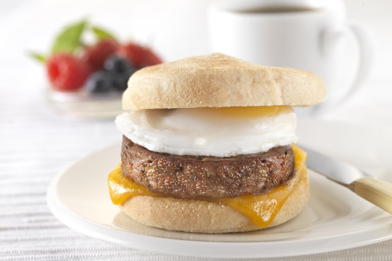 A muffin filled with a Quorn Sausage Patty, a slice of melted cheese, and a fried egg on a white plate.