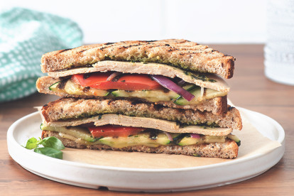 A panini filled with Quorn Meatless Turkey-Style Deli Slices, red pepper, red onion, zucchini, pesto, and cheese.