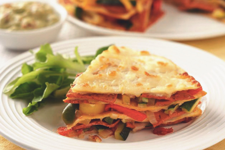 A slice of vegetarian tortilla layered with Quorn Pepperoni Slices, courgettes and peppers served on a plate