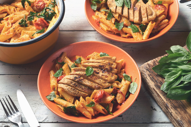 A coral bowl filled with penne pasta in a tomato sauce topped with spinach, basil, and a sliced Quorn Fillet with another identical bowl and the serving bowl of pasta in the background.