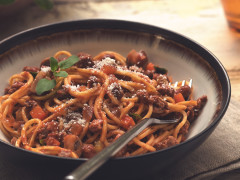 A bowl of spaghetti Bolognese made with Quorn Grounds topped with basil and Parmesan cheese.
