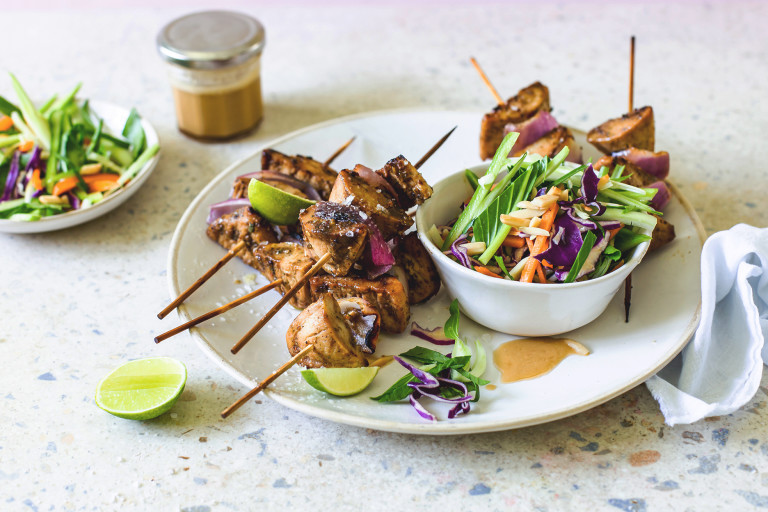 Quorn Pieces and red onion skewers piled high on a white plate with a bowl of red cabbage, carrot, cucumber, and bok choy slaw on the side with lime wedges for serving and dressing in the background.