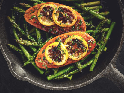 Quorn Fillets topped with lemon slices atop a bed of asparagus in a cast iron skillet.