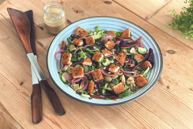 A garden salad topped with pumpkin seeds and diced Quorn Vegan Hot & Spicy burger patties.