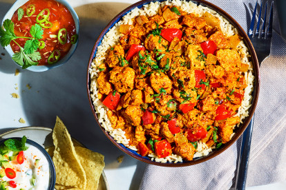 Veggie tikka masala made with Quorn Pieces served in a silver dish with handles next to a bowl of rice