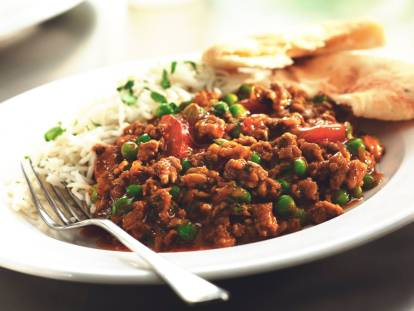 Keema curry with peas served alongside rice and flatbread.