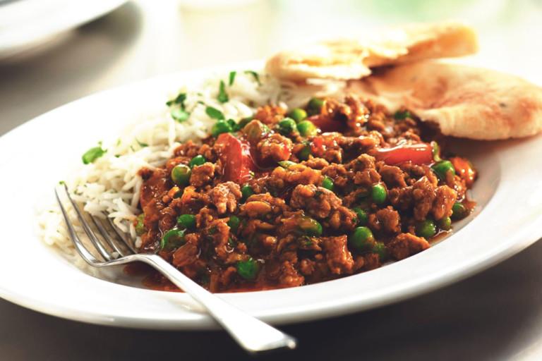 Keema curry with peas served alongside rice and flatbread.
