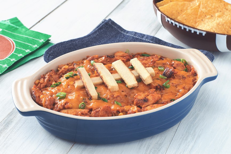 A blue oblong-shaped dish filled with bbq chickenless dip with Quorn Fillet slices arranged on top to make the dish resemble a football.
