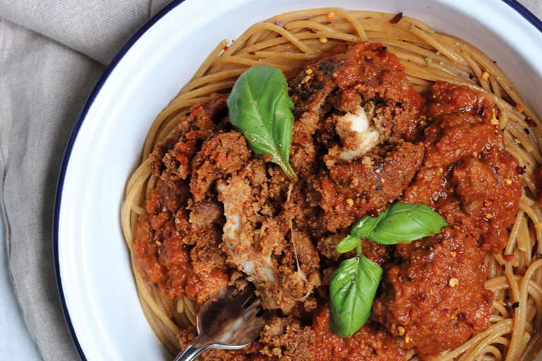 Meat-free meatballs made with Quorn Mince and stuffed with mozzarella cheese sit atop vegetarian arrabiata sauce and whole-wheat spaghetti in an enamel dish garnished with basil.