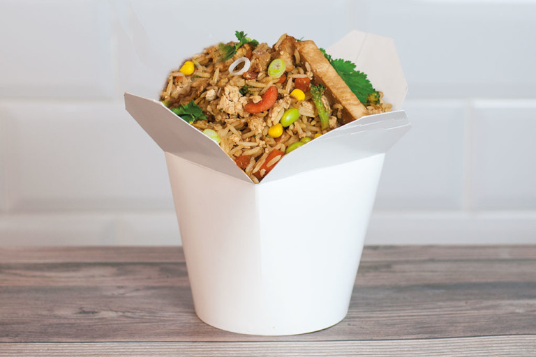 A white Chinese takeout container filled with air fryer fried rice made with Quorn Vegan Fillets.