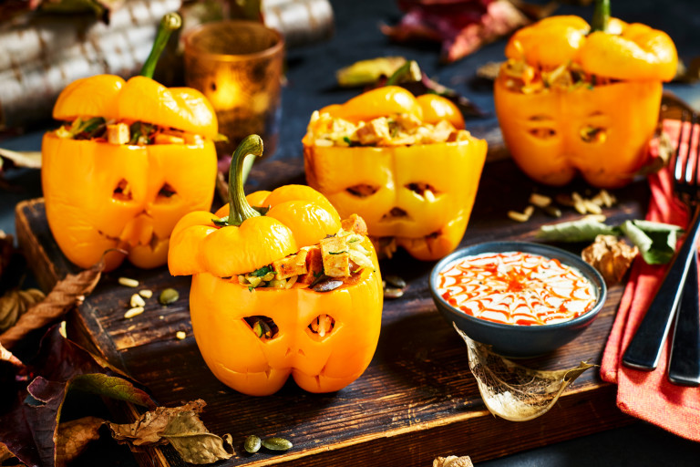 Four yellow peppers carved like jack-o-lanterns and stuffed with wild rice, vegetables, and diced Quorn Cocktail Sausages.