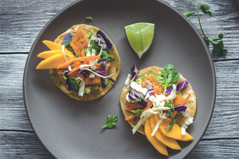 Two tostadas topped with Quorn Fishless Sticks, avocado, mango, and salw with a wedge of lime on the side.