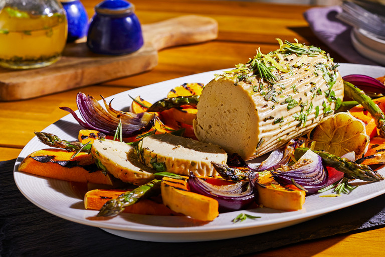 A summer vegetarian roast made with Quorn Roast topped with rosemary and lemon zest in the centre of a platter surrounded by roasted vegetables.
