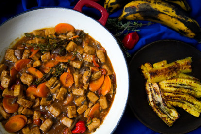 A red Dutch oven filled with Jamaican Brown Stew made with Quorn Vegan Pieces, sliced carrots, scotch bonnet chilli, and thyme on a blue background with a dish of plantain on the side.