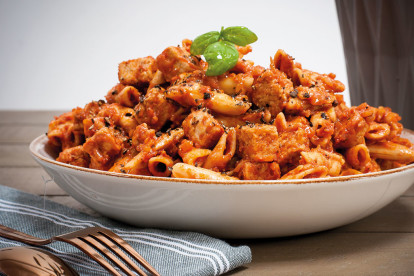 A bowl of one pot pasta made with penne pasta and Quorn Vegan Pieces in a tomato-based sauce garnished with a sprig of basil.