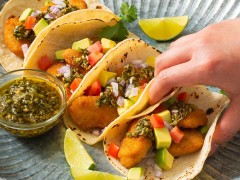 Four tacos filled with air-fried Quorn Crispy Nuggets and diced avocado, tomato, and onion, and topped with chimichurri sauce with extra sauce and lime wedges on the side.