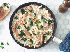 A pan full of penne in alfredo sauce with kale, Quorn Strips, and Parmesan cheese on a white tile background with a wooden spoon and pepper grinder on either side.