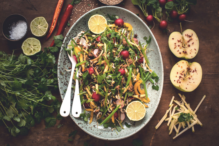 A salad with sugar snap peas, green apple, radishes, bean sprouts, green onions, and Quorn Meatless Grounds with the ingredients arranged around the serving dish,