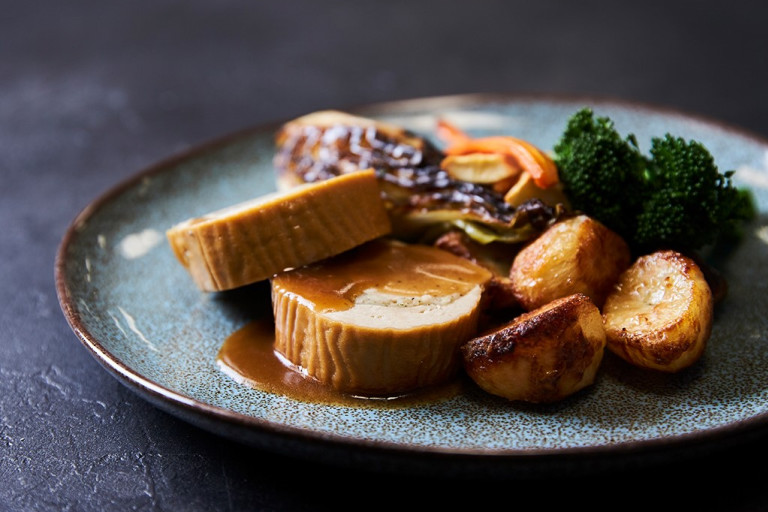 Two slices of a Quorn Roast stuffed with vegetarian stuffing served with roasted potatoes, roasted carrots and parsnips, broccoli, and roasted cabbage on the side and topped with gravy.