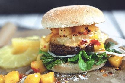 Veggie burger recipe made with Quorn Classic Beef Style Burger on top of lettuce garnished with onions, pineapple and mango salsa in a bun
