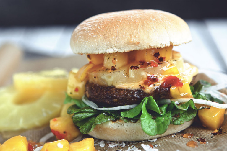 Veggie burger recipe made with Quorn Quarter Pounders on top of lettuce garnished with onions, pineapple and mango salsa in a bun