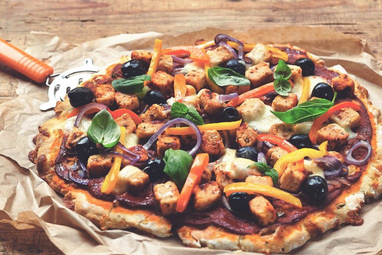 A meat free pizza topped with Quorn pieces resting on baking paper with a pizza cutter beside the pizza.