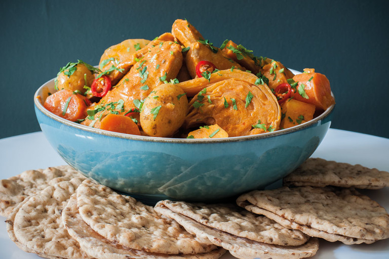 A blue bowl of Senegalese mafe made with Quorn Vegan Pieces and vegetables with small flatbreads on the side.